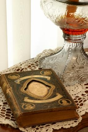 Antique book, lamp and doilies on table
