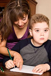 Mother helps her autistic son with schoolwork.