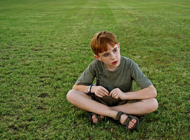 boy sitting alone on grass