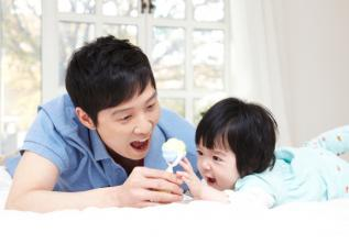 Father and baby playing with a rattle