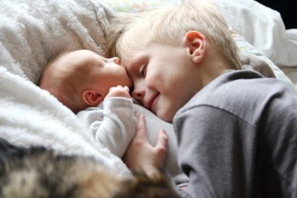 Big brother loving newborn baby