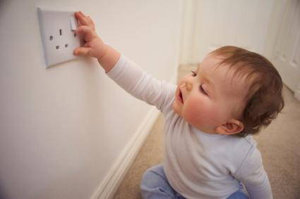 Toddler playing with plug socket
