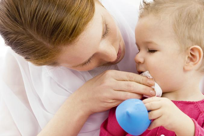 woman wiping baby's mouth