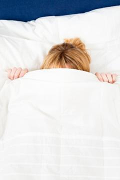 Woman lying underneath a down comforter