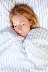 Woman snuggling under comforter.