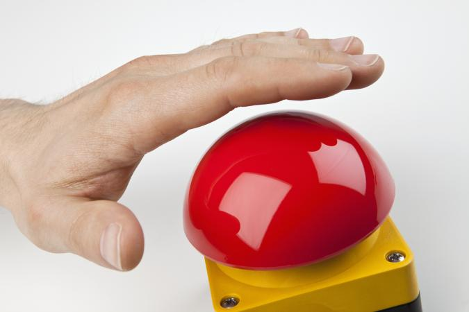 A hand about to press buzzer