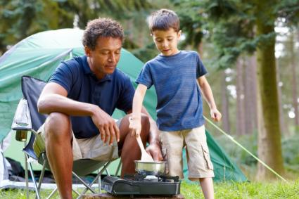 Father and son cooking breakfast on camping trip