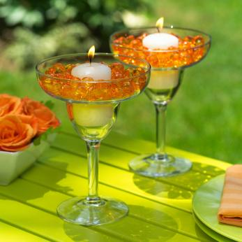 Cocktail glasses filled with glass beads and a candle in the center