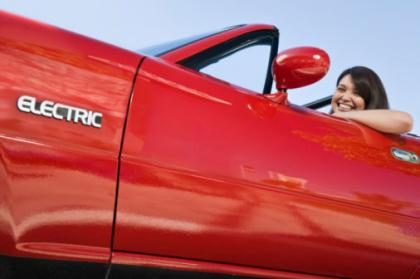 Smiling woman in red electric car
