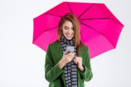 Woman using smartphone under umbrella