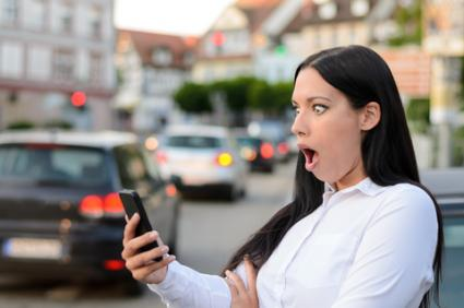 Astonished woman reading sms on mobile