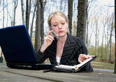 Businesswoman talking on phone while working outside