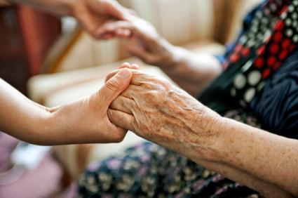 Volunteer holding elderly person's hand