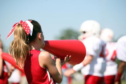 Cheerleader with megaphone and players in the background
