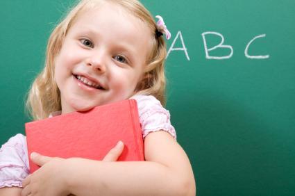 Little girl hugging her alphabet book