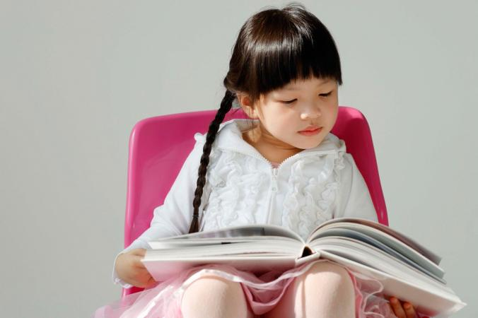 Young girl seated reading