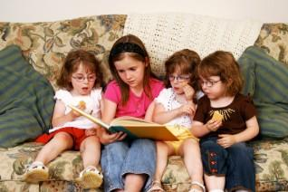 Children reading a book together.