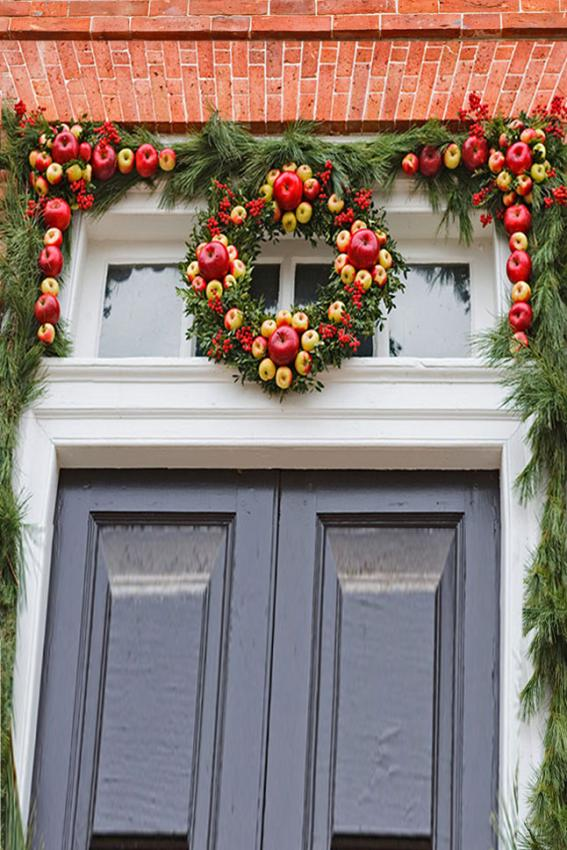 doorway with christmas wreath of apples and pine boughs