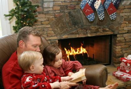 Dad and children reading by fireplace