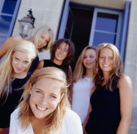 Group of college women in front of house