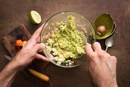 Mashing vegetables to make guacamole