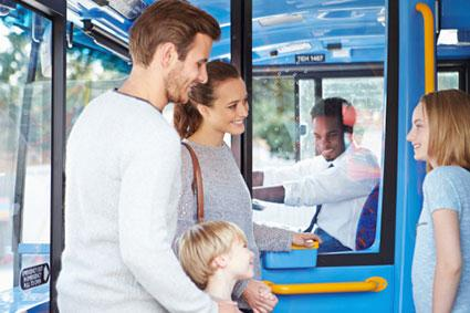 family boarding bus and buying ticket