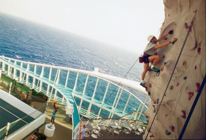 Man climbing on rock wall on Royal Caribbean Voyager