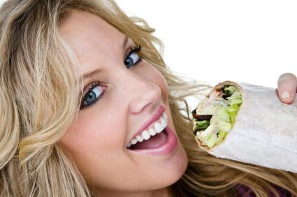 Woman eating a healthy wrap.