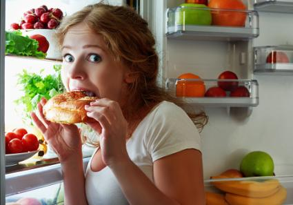 Woman eating from the refrigerator