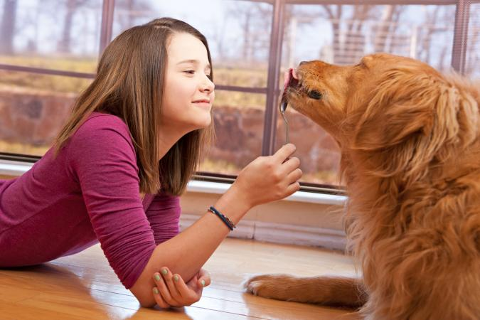 Young Girl Feeds Her Dog