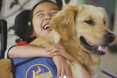 Girl laughing with her service dog; Image used with permission from Jeanine Konopelski.