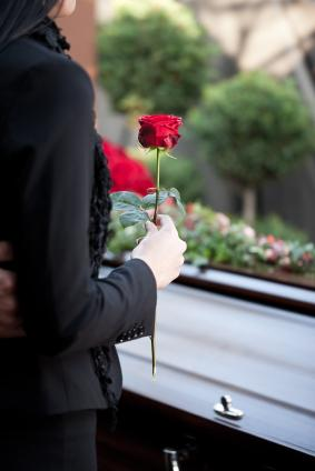 Woman holding a rose at a burial