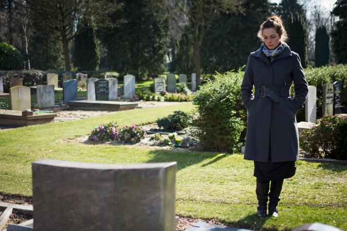 Woman grieving at cemetery