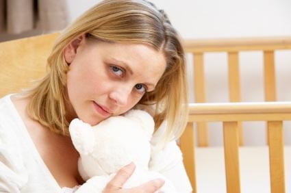 mother holding teddy bear empty nursery
