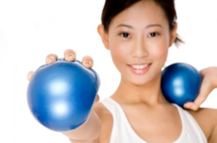 Woman holding two small weighted balls