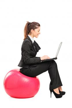 woman sitting on exercise ball in suit, typing