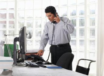 Male using telephone, standing at desk
