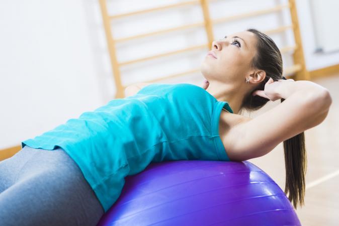 Woman exercising at home on a balance ball
