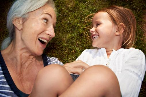 Grandmother and granddaughter lying in grass