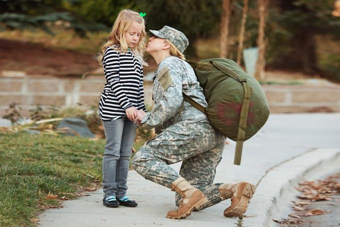 Military mother kissing her daughter goodbye