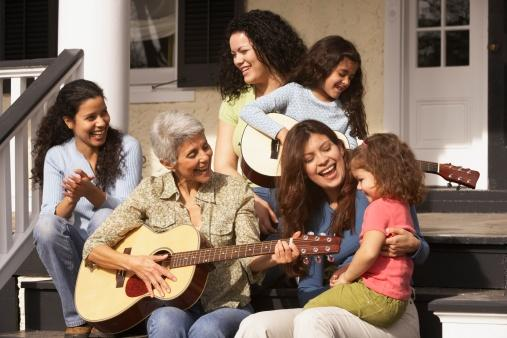 family sitting on porch playing guitar