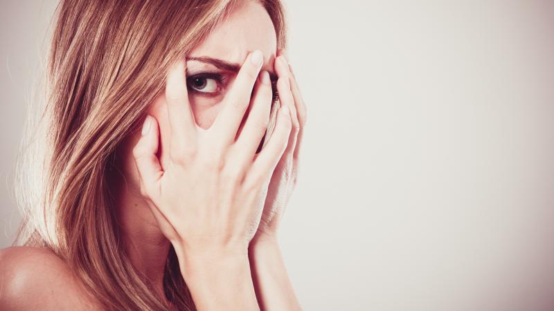 Woman peeking through her fingers