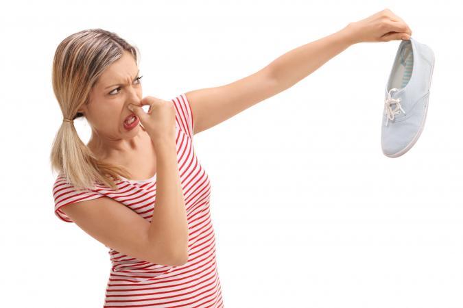 Woman holding a stinky shoe