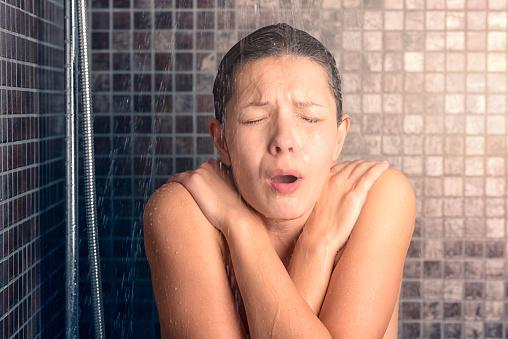 Woman Reacting While Taking Cold Shower