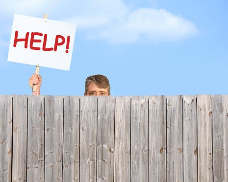 Man with HELP sign looking over fence