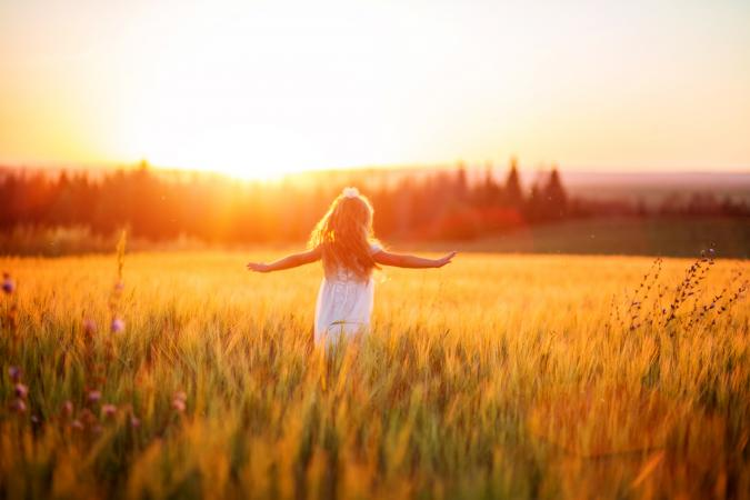 Little girl in white dress in field at sunset