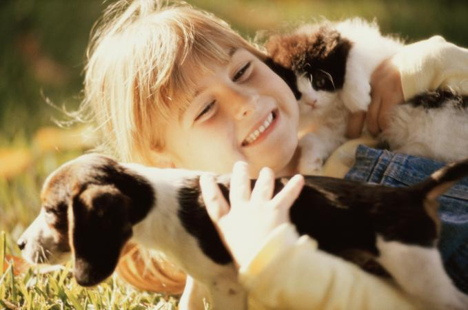 Girl holding a puppy and a kitten