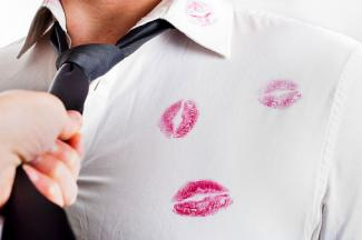 Man in white shirt covered by red lipstick kisses