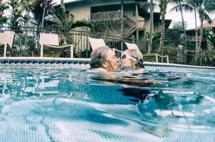 Retired couple in pool kissing