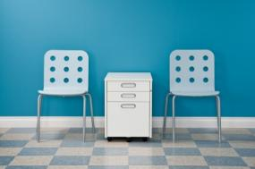 White filing cabinet between two chairs